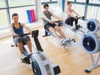 People using rowing machines in fitness studio